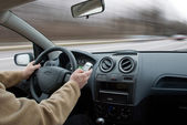 Driver using cell phone in car blurred motion — Stock Photo