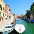 Aquamarine canal with boats in Venice - Stock Photo
