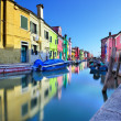Canal and colorful houses of Burano island in Venice - Stock Photo
