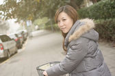 Young Asian woman riding bicycle — Stock Photo