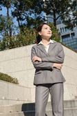 Confident Asian business woman standing in outside of office in — Stock Photo
