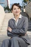 Sorridente negócios asiáticos mulher sentar na escada — Fotografia Stock