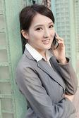 Asian business woman talking on smart phone — Stock Photo