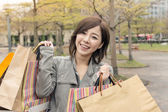 Asian woman walk and hold shopping bags — Stock Photo