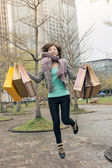 Happy smiling shopping woman jumping — Stock Photo