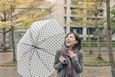 Happy smiling Asian woman holding an umbrella — Stock Photo