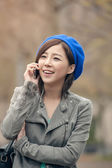 Cheerful Asian lady talking on cellphone at street in the park, — Stock Photo