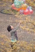 Young woman playing and holding balloons — Stock Photo