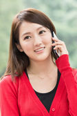 Smiling Asian young woman take a call — Stock Photo