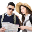 Stock Photo: Young Asicouple travelers looking map