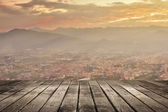 City sunset with wooden ground — Stock Photo