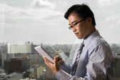 Asian businessman using tablet — Stock Photo