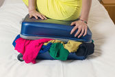 Close the overfilled suitcase — Zdjęcie stockowe