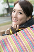 Attractive Asian young woman shopping and holding bags — Stock Photo