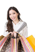 Attractive asian woman holding shopping bags — Stock Photo