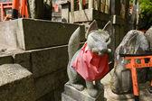 Stone fox statues  and many small torii. — Stock Photo