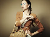 Portrait of beautiful young woman with a leather bag — Стоковое фото