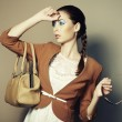 Portrait of beautiful young woman with a leather bag - Stock Photo