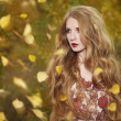 Fashion portrait of a beautiful young woman in autumn forest — Stock Photo