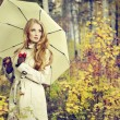 Fashion portrait of a beautiful young woman in autumn forest — Stock Photo #13628404