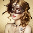 Beautiful young woman in brown mysterious venetian mask — Stockfoto