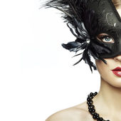 Beautiful young woman in black mysterious venetian mask — Stok fotoğraf