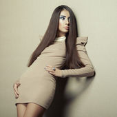 Fashion photo of young sensual woman in beige dress — Stock Photo