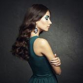 Portrait of beautiful brunette woman in green dress — Stock Photo