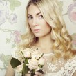 Portrait of a beautiful blonde woman with flowers — Stock Photo