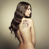 Portrait nude young woman with tattoo — Stock Photo