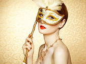 Beautiful young woman in mysterious golden Venetian mask — Stock Photo