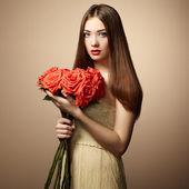 Portrait of beautiful dark-haired woman with flowers — Zdjęcie stockowe