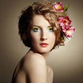 Beautiful young woman with delicate flowers in their hair — Stock Photo