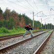 An elderly man crosses a railway embankment — Stock Photo #22925686