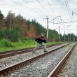 An elderly man crosses a railway embankment - Stock Photo