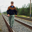 An elderly man walking on tracks - Stock Photo