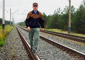 An elderly man walking on tracks — Stock Photo