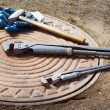 Stockfoto: Hammer and wrench are on manhole
