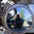 Two motorcyclists are reflected in brilliant motor — Stock Photo
