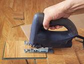 Master using an electric jigsaw saws laminated panel — Stock Photo