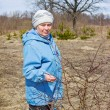 Elderly woman in a spring forest — Stock Photo