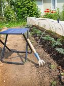 Folding chair and rake — Stock Photo