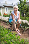 Elderly woman removes the weeds in the garden — Stock Photo