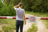 Man stands in front of a barrier in the forest — Stock Photo