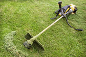 Petrol trimmer is on the sloped lawn — Stock Photo