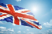 Union jack in the blue sky — Stock Photo