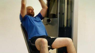 Vuxen man använder hemma gymutrustning för att stärka sina bröstmuskler. — Stockvideo