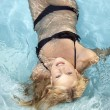 Active young blonde woman in a blue pool — Stock Photo