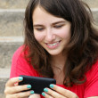 Young woman smiling at cell phone — Foto de Stock