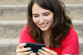 Young woman smiling at cell phone — Stock Photo